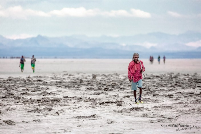 Afar saltminer walks through salt lake - copyright Krijn van der Giessen Photography