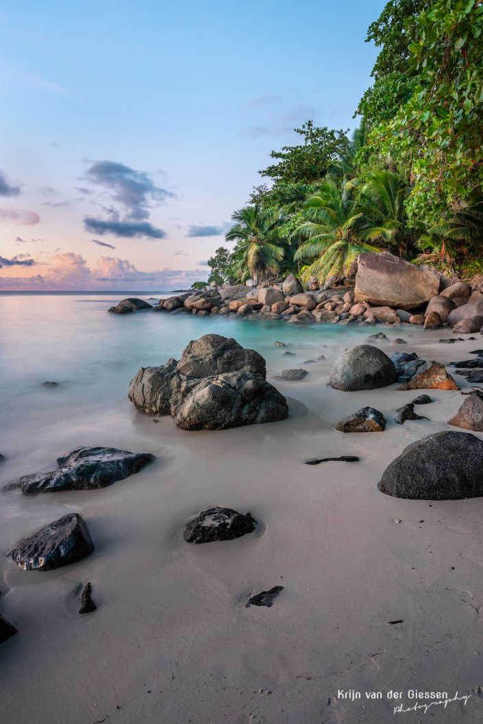 Seychelles beach with boulders and palm trees during sunset