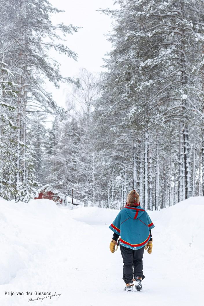 Sami woman walks through snow in Sweden Lapland Copyright by Krijn van der Giessen Photography